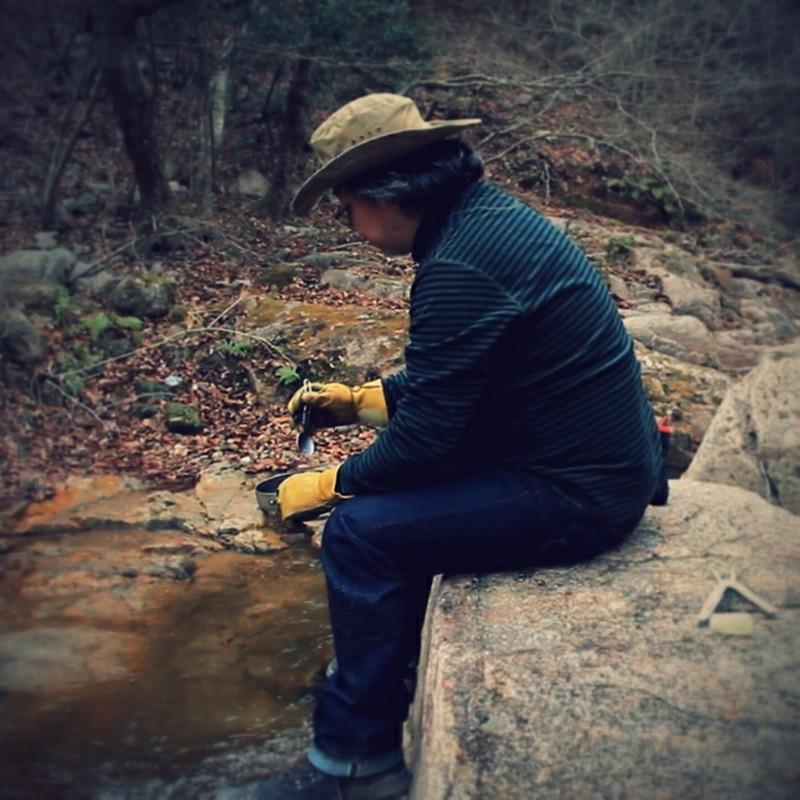 真冬の山中の川っぺりで、一人、なにかをモクモクと食ってるデブのポートレイト