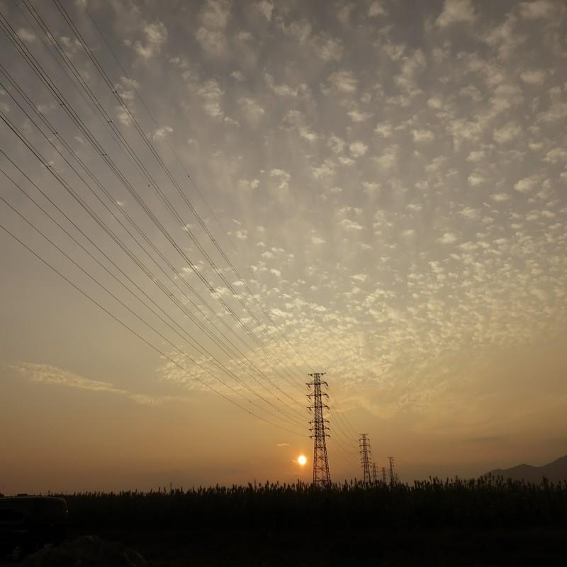 秋の日、雲と夕日と鉄塔